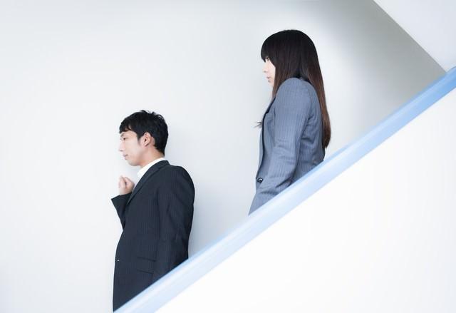 オフィスの非常階段を下りながら非常に重要な件をする人事部長の写真