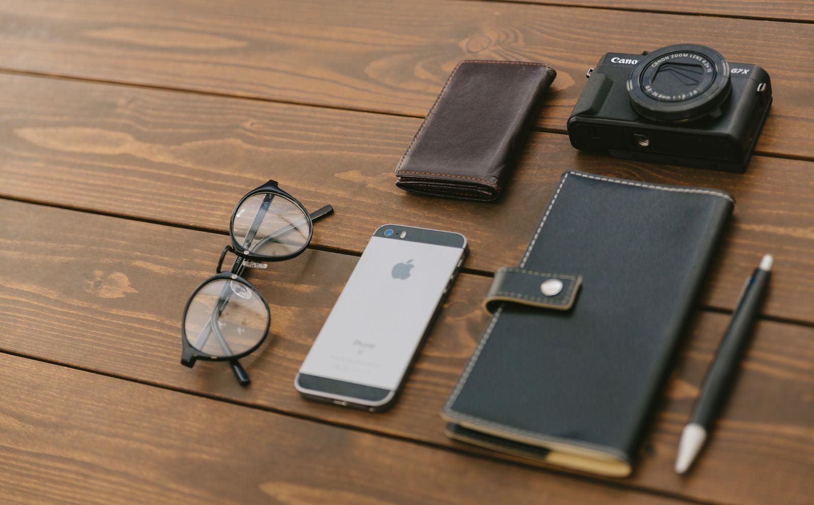 「木目のテーブルに置かれた手帳やカメラ木目のテーブルに置かれた手帳やカメラ」のフリー写真素材を拡大