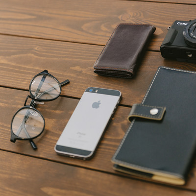 「木目のテーブルに置かれた手帳やカメラ」の写真素材