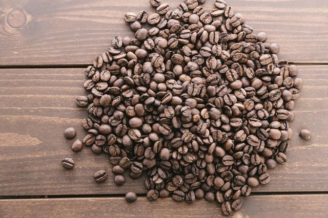 木目のテーブルとコーヒー豆の写真
