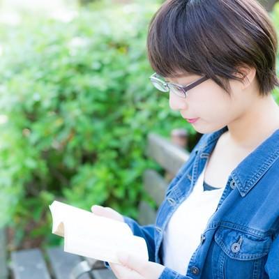 公園のベンチで読書をする文学少女の写真