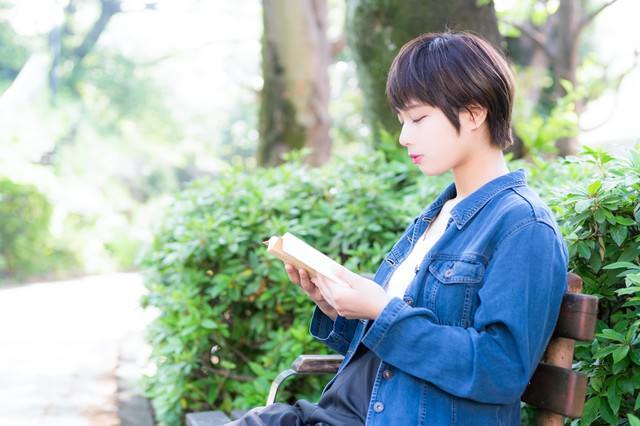 ライトノベルを読みながら彼氏を待つ健気な女性の写真