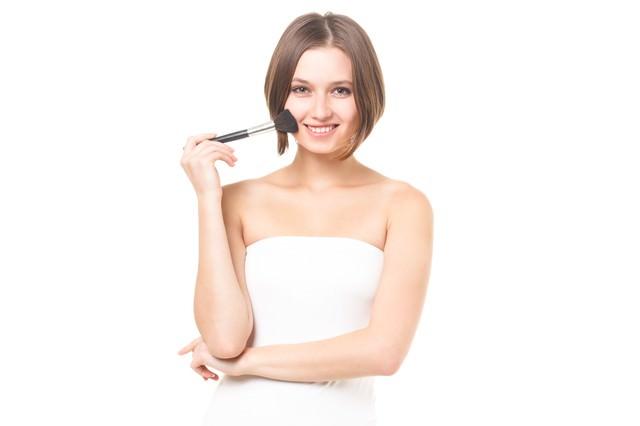 チークブラシを持って微笑む女性の写真