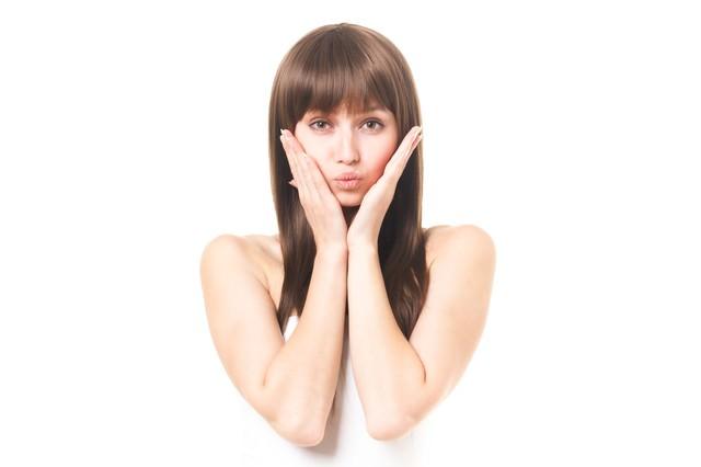 両手を頬にスキンケアを強調する女性(エステ・美容)の写真