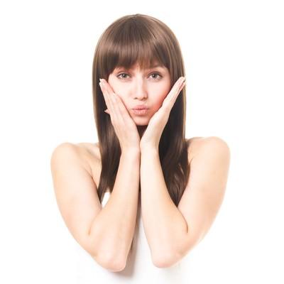 「両手を頬にスキンケアを強調する女性(エステ・美容)」の写真素材