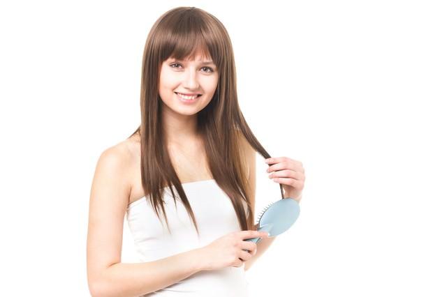 クシで髪の毛をとかす外国人の女性の写真