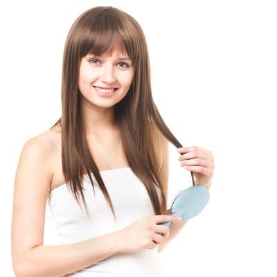 「クシで髪の毛をとかす外国人の女性」の写真素材