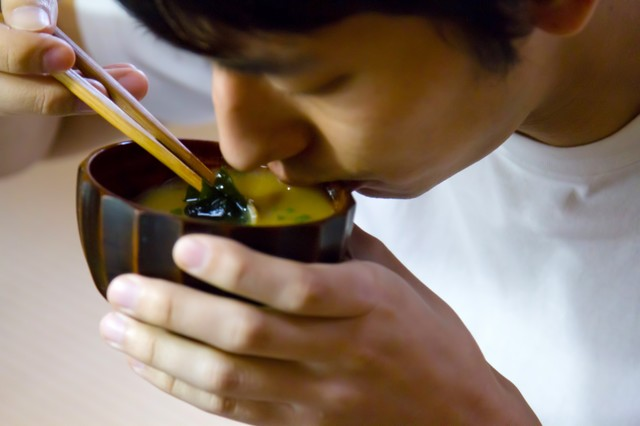 お味噌汁をすする男性の写真