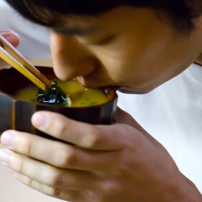「お味噌汁をすする男性」の写真素材