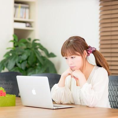 コワーキングスペースでMBAで作業する女性の写真