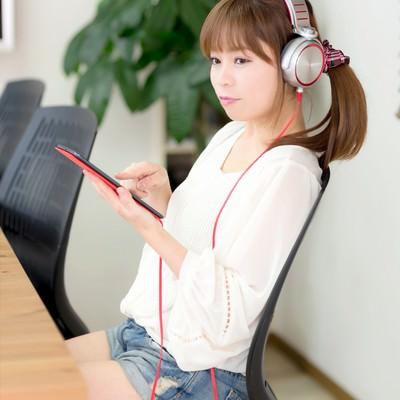 「iPad mini で音楽を聴くホットパンツの女性」の写真素材