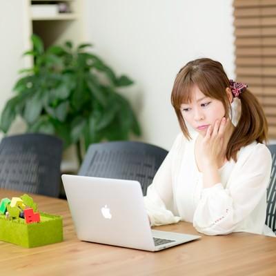 「電源完備のコワーキングスペースで作業をする女性」の写真素材