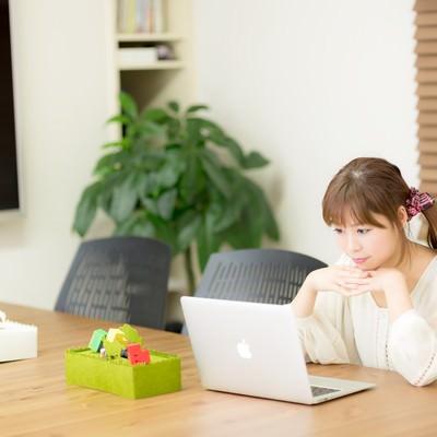 「清潔感のあるコワーキングスペースで作業をする若い女性」の写真素材