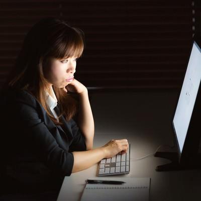 「消灯の中、残業してモニターを見つめる女性」の写真素材
