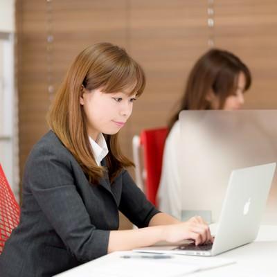 「コワーキングスペースでちゃんと仕事する女性」の写真素材