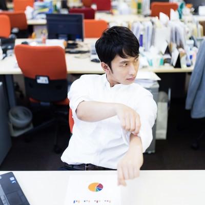 「ワイシャツの袖をまくりながらドヤ顔をする会計士」の写真素材