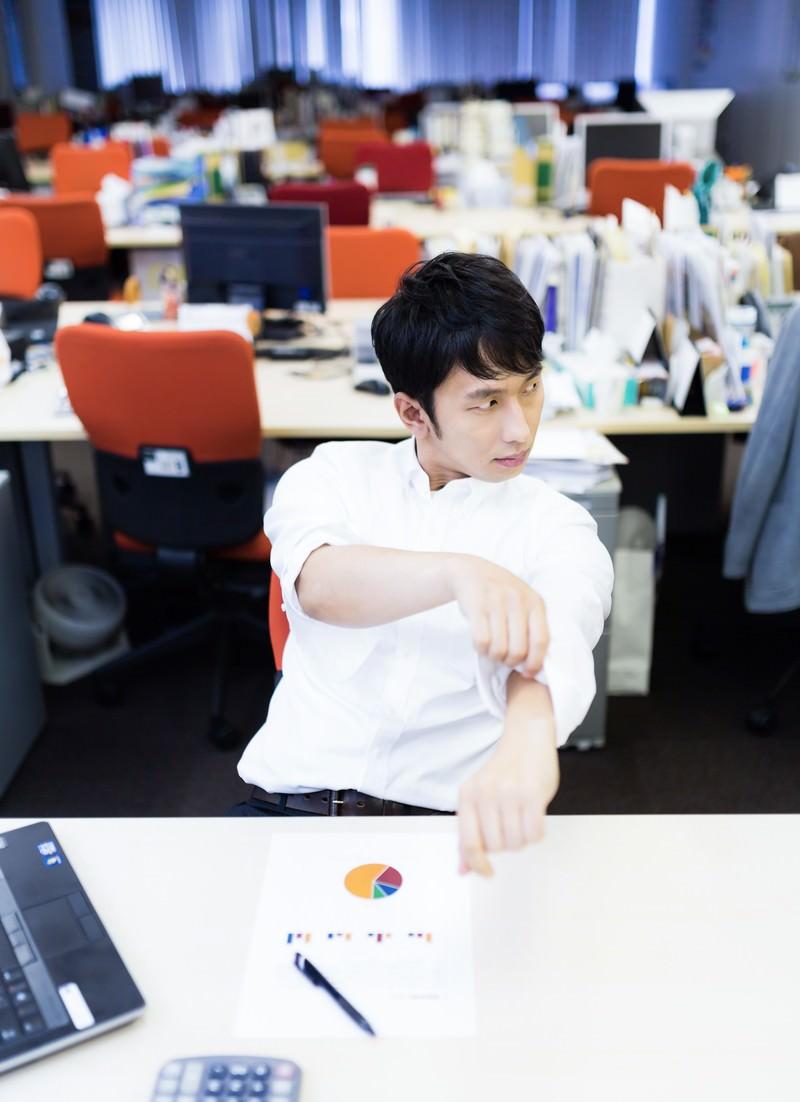「ワイシャツの袖をまくりながらドヤ顔をする会計士」の写真[モデル:大川竜弥]