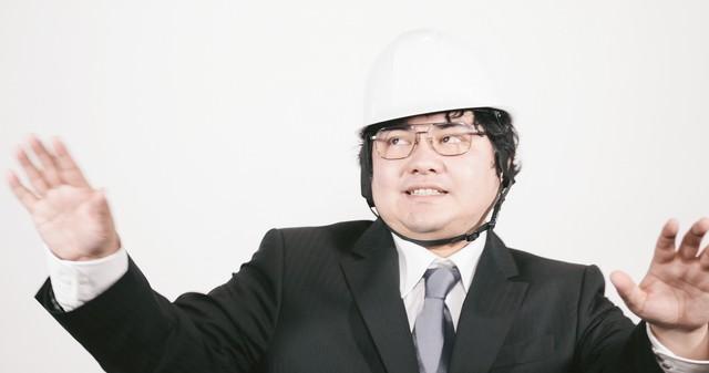冷静沈着を呼びかけるヘルメットをかぶった職員の写真