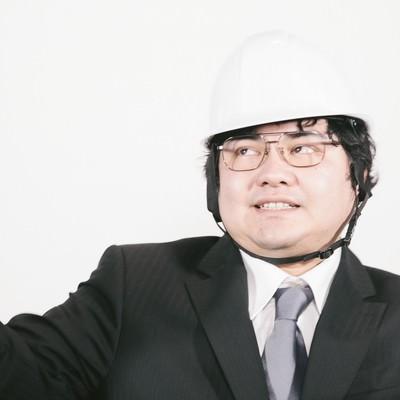 「冷静沈着を呼びかけるヘルメットをかぶった職員」の写真素材