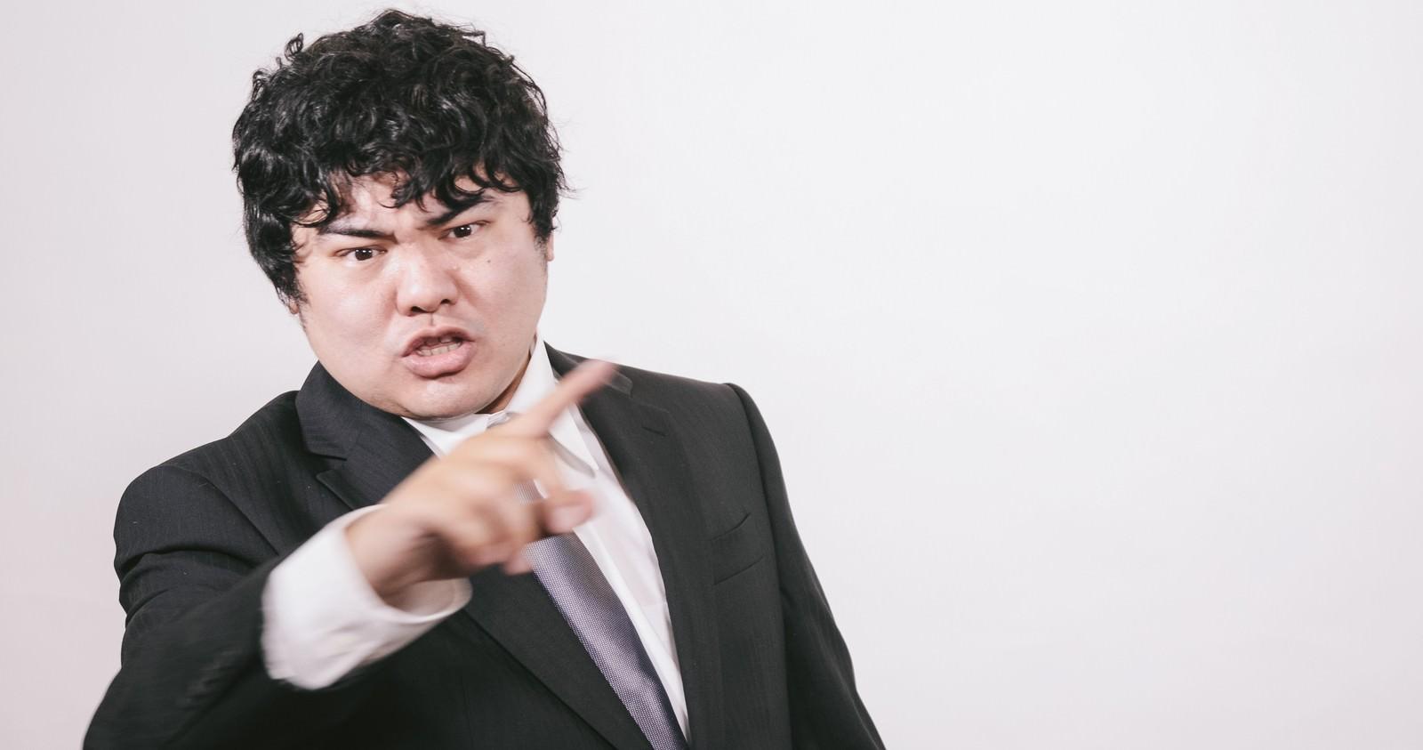 「ズバッと指摘するサラリーマン」の写真[モデル:段田隼人]