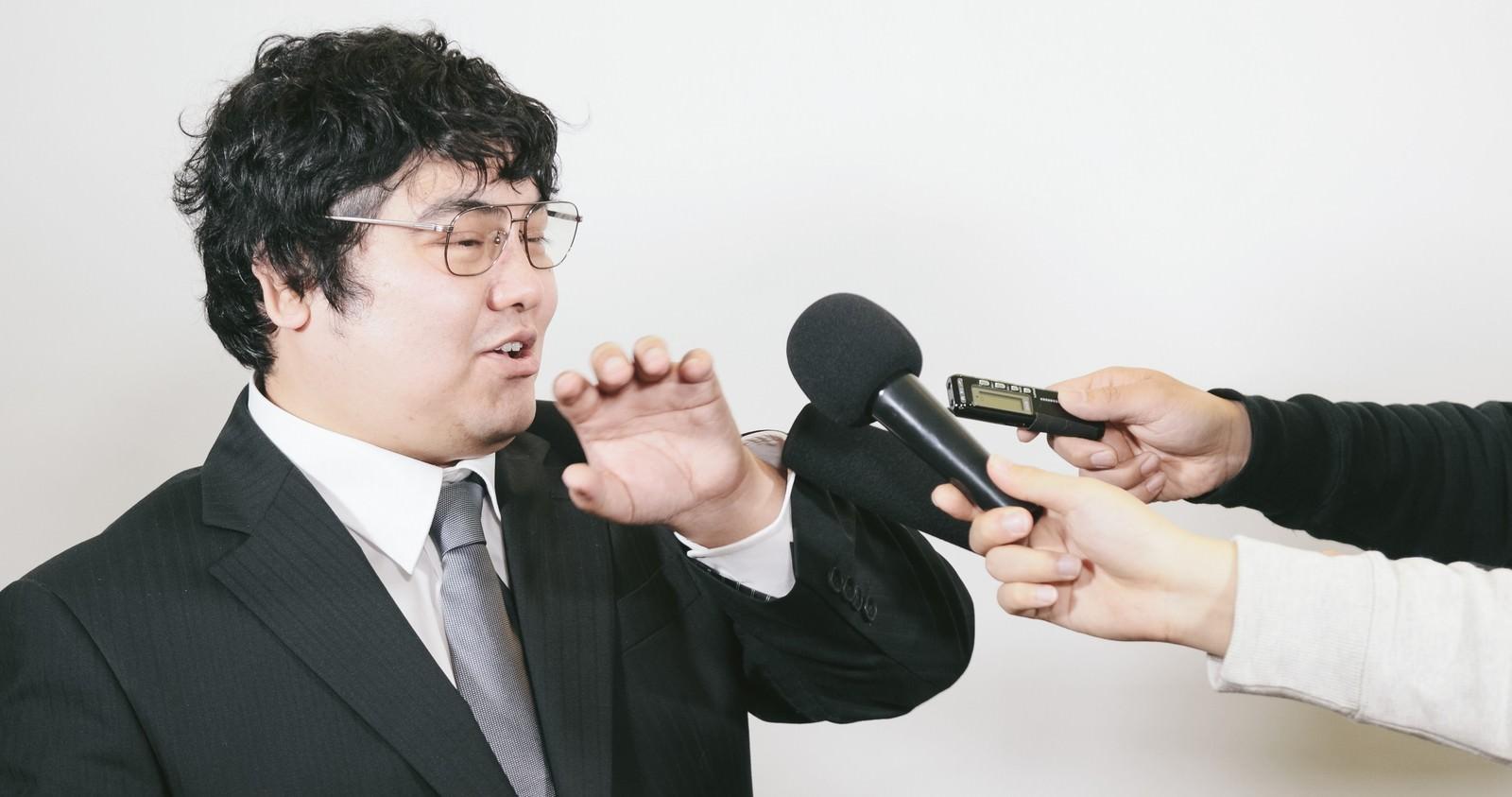 「マイクを突きつけられる会社役員」の写真[モデル:段田隼人]
