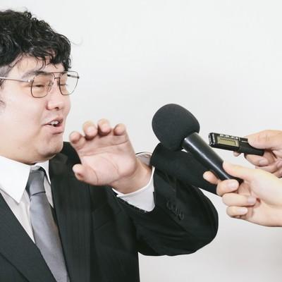 マイクを突きつけられる会社役員の写真