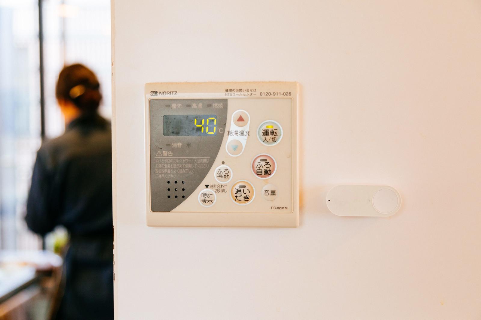 「湯沸かし器の横に取り付けられたダッシュボタン」の写真