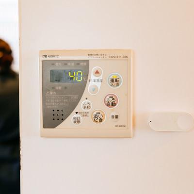 「湯沸かし器の横に取り付けられたダッシュボタン」の写真素材