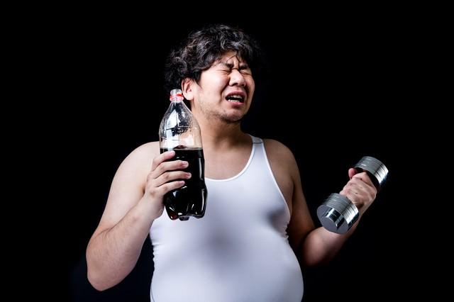 コーラの重さでダンベルの重さを決めるダイエッターの写真