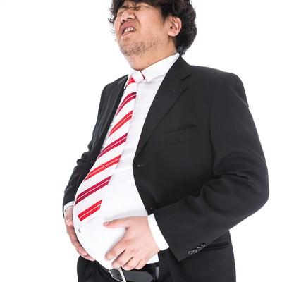 「ラーメン餃子セットにご飯を追加したことを後悔している部長」の写真素材