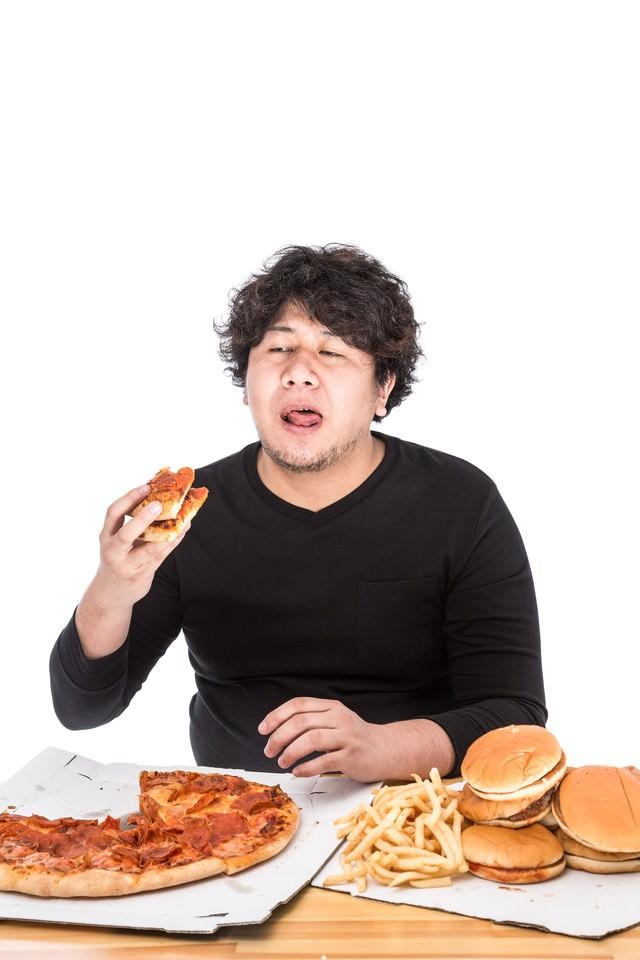100枚目のピザにうんざりしている大食いファイターの写真