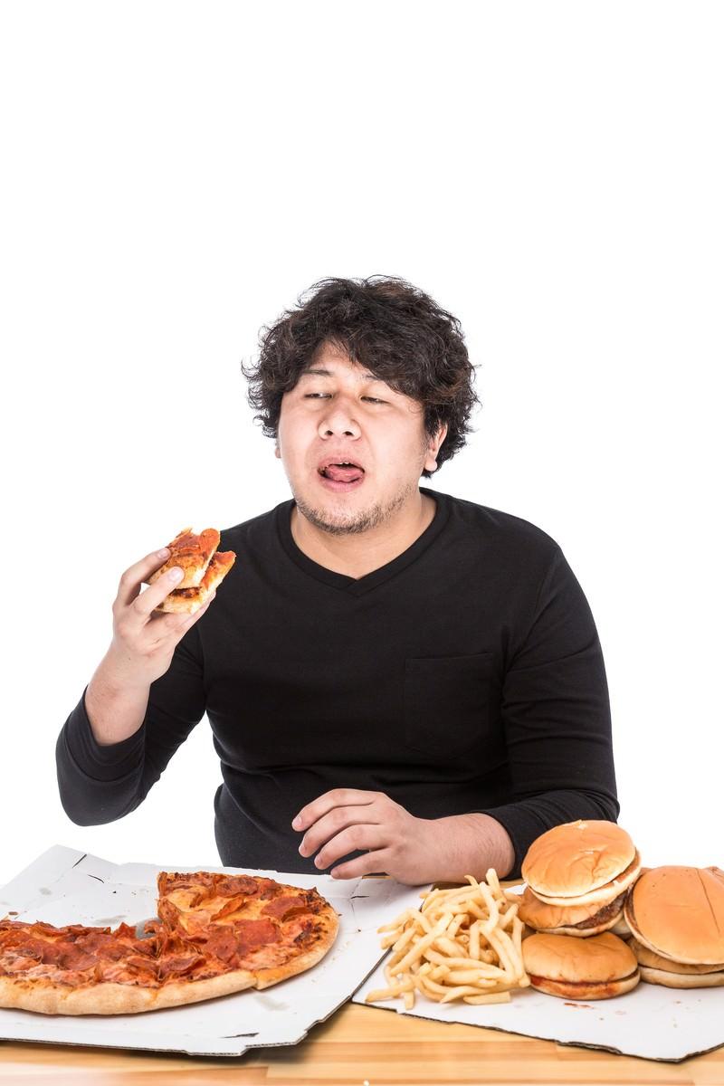 「100枚目のピザにうんざりしている大食いファイター」の写真[モデル:朽木誠一郎]