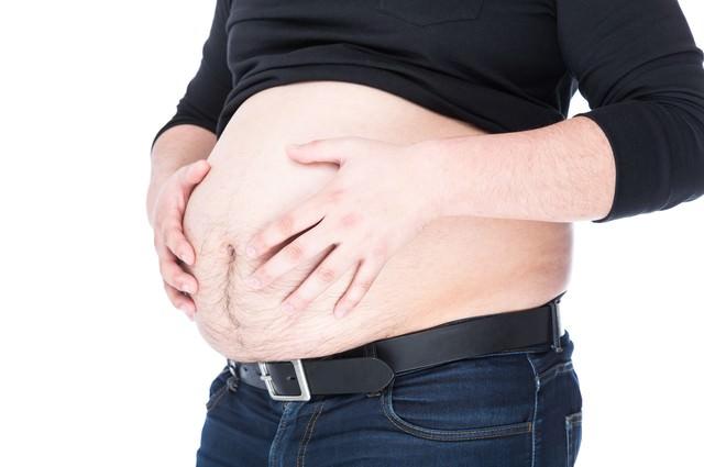 ハンドパワーで腹部をへこませようとする肥満ジシャンの写真