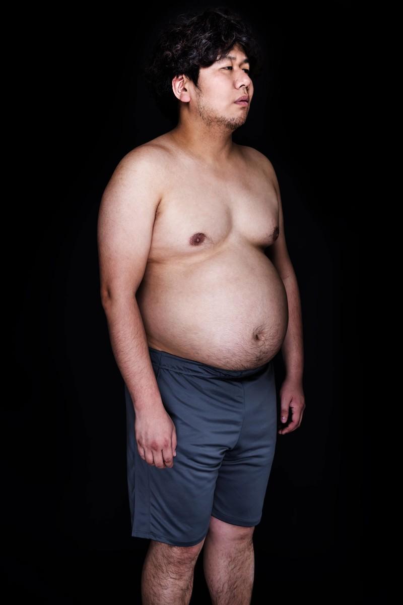 「皮下脂肪たっぷりの腹部と同じ表情をするリアルマリオネット」の写真[モデル:朽木誠一郎]