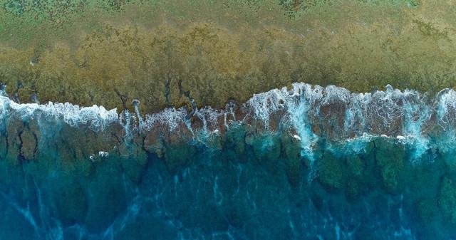 徳之島の珊瑚礁に囲まれた透明感ある海と波(空撮)の写真