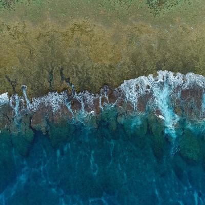 「徳之島の珊瑚礁に囲まれた透明感ある海と波(空撮)」の写真素材