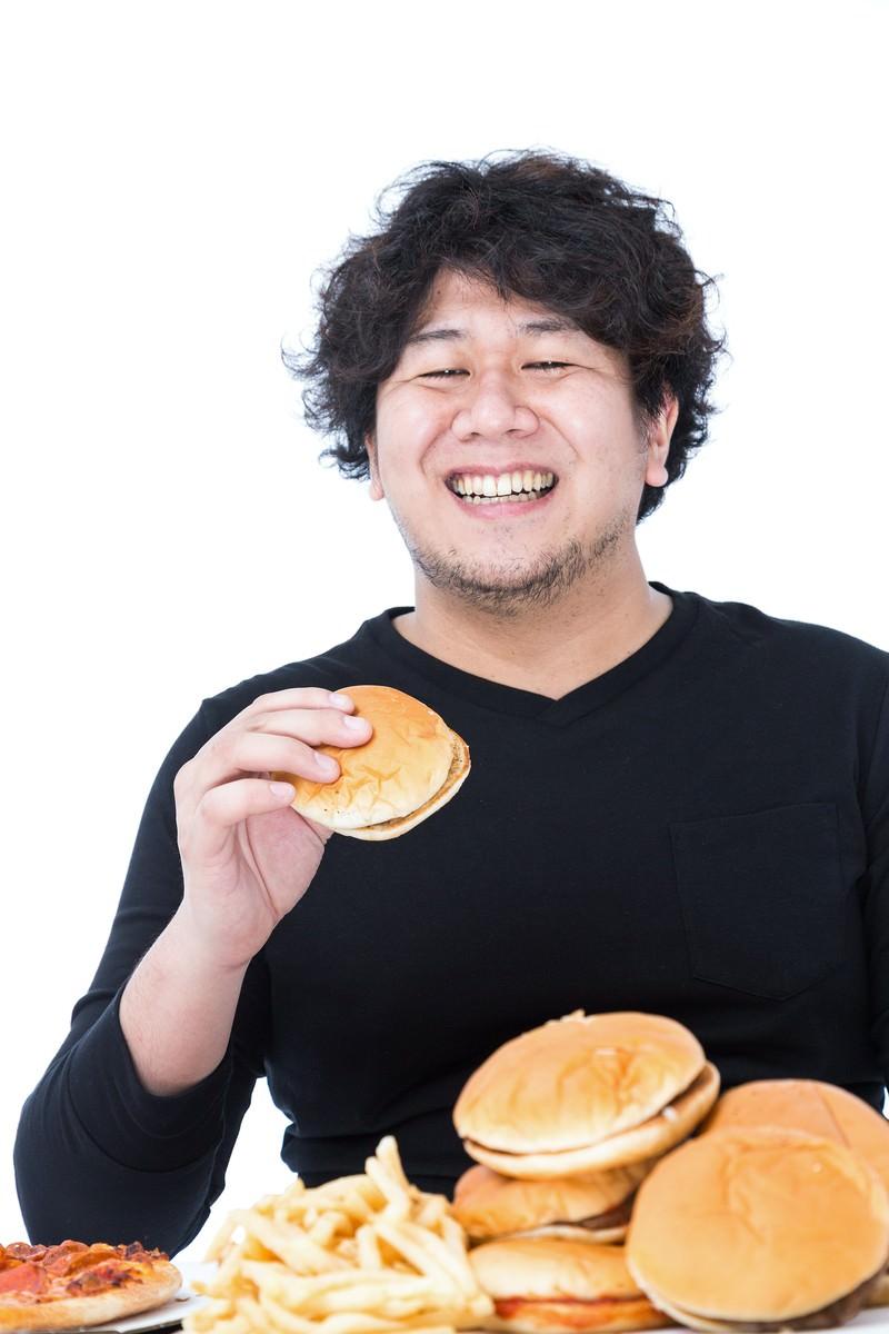 「ハンバーガーの山を登頂する食のクライマー」の写真[モデル:朽木誠一郎]