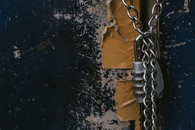 南京錠でロックしている意味がないくらいテープで補強されたドアの写真