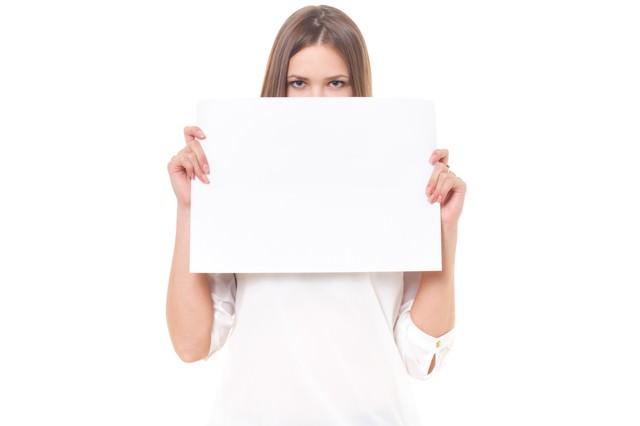 白い紙(案内)を持った外国人の女性の写真