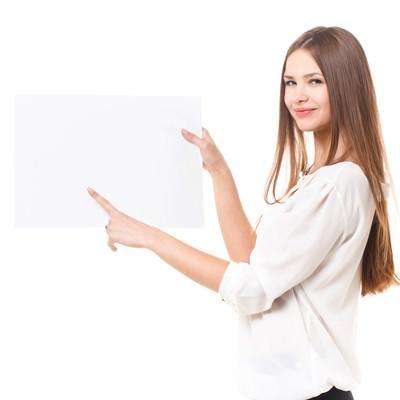 「白いボードに指をさす外国人の女性」の写真素材