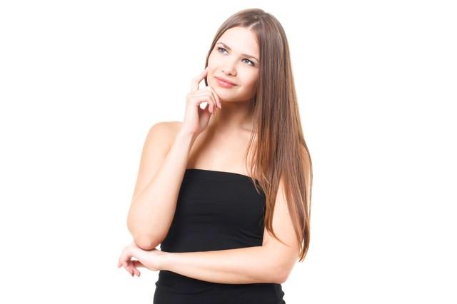 上を向いて考える若い外国人の女性の写真