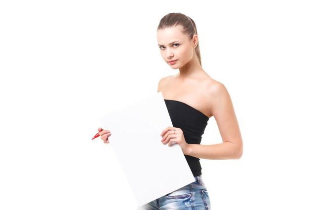 白いボードを手に持った外国人の女性の写真