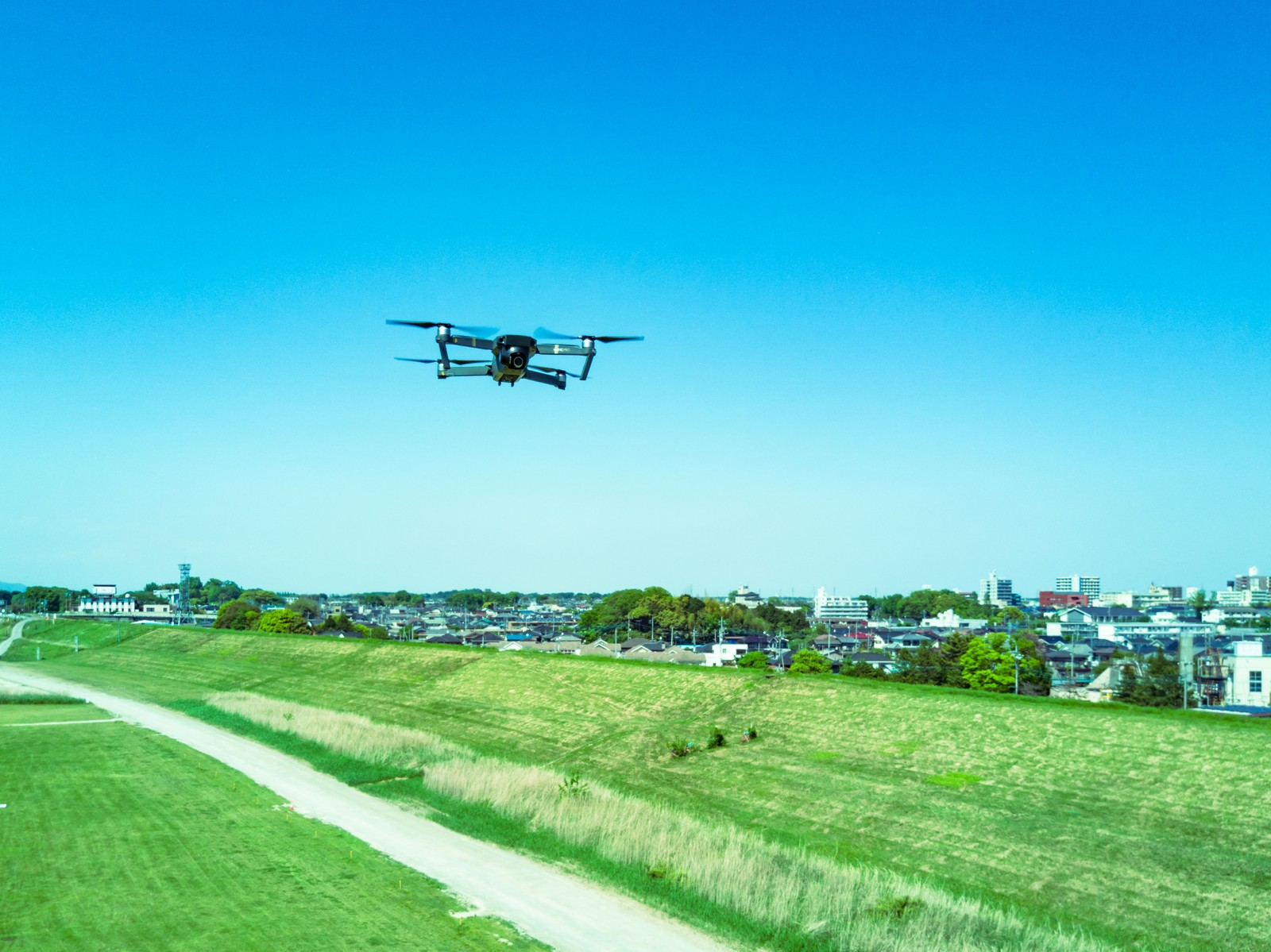 「河川敷でマルチコプター(ドローン)が飛行中」の写真
