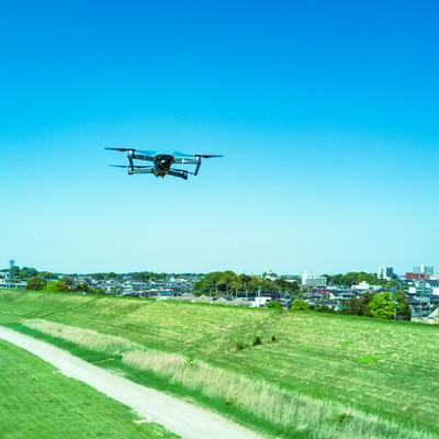河川敷でマルチコプター(ドローン)が飛行中の写真