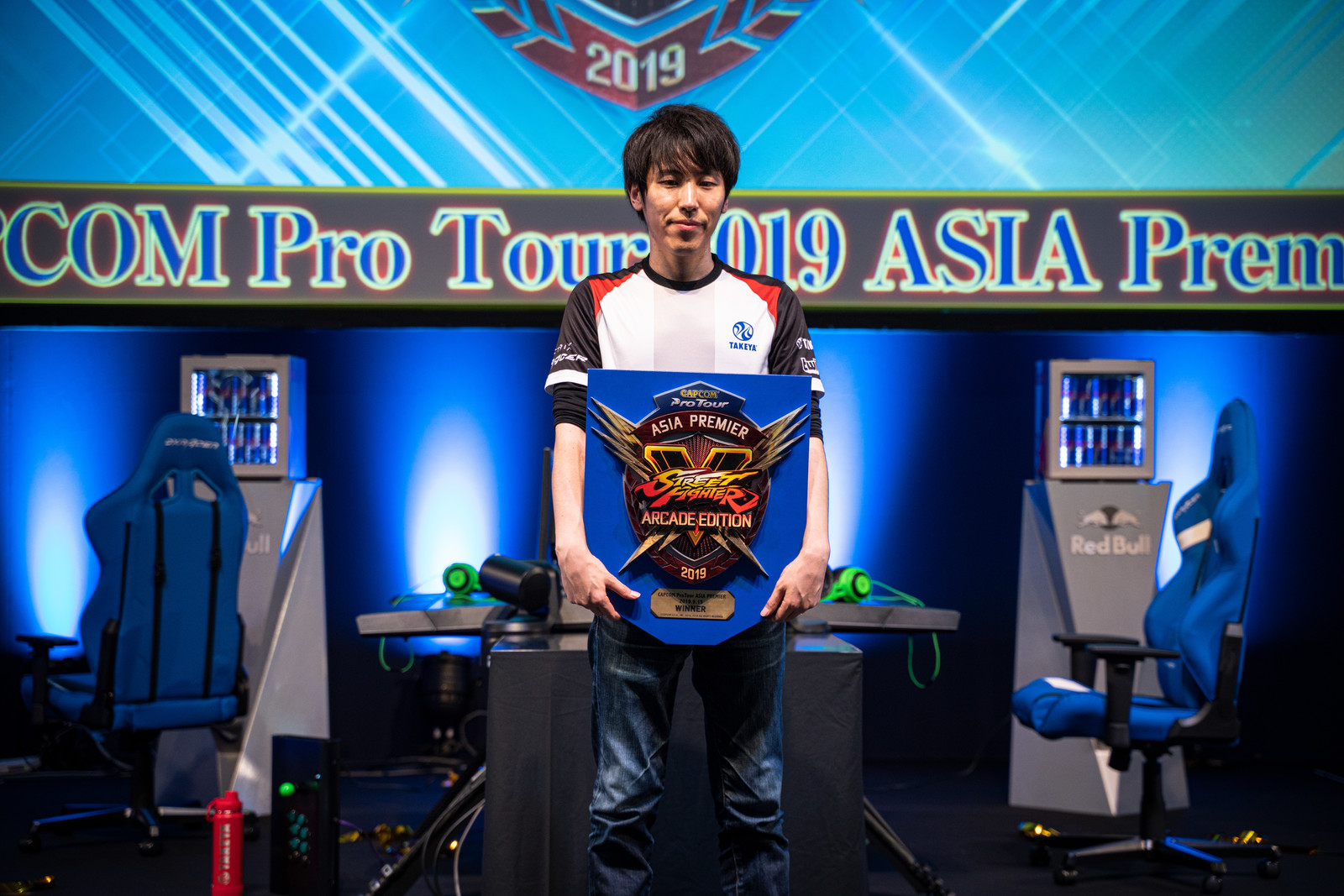「優勝盾を両手で持つ大会チャンピオンももち選手 - CAPCOM Pro Tour 2019 アジアプレミア」の写真