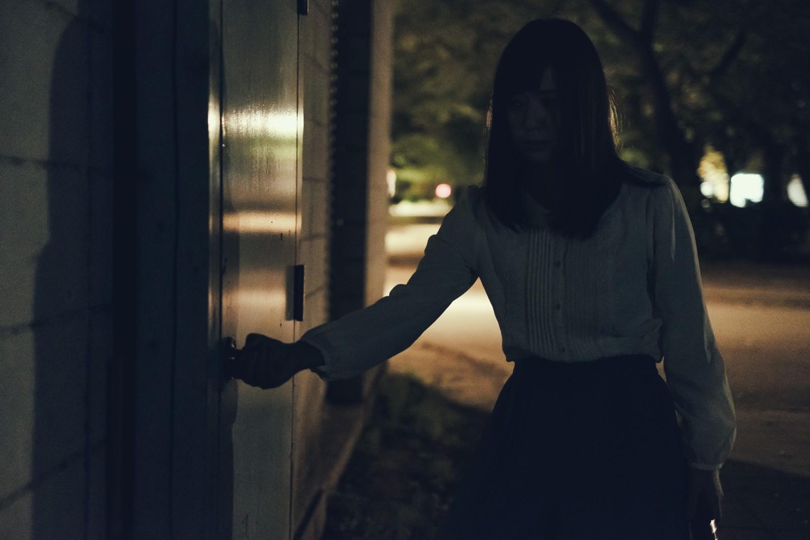 「深夜に倉庫の扉を開ける女性」の写真[モデル:さとうゆい]