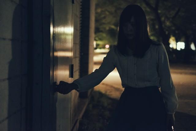 深夜に倉庫の扉を開ける女性の写真