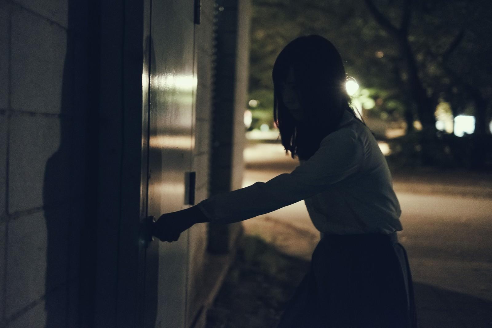 「意を決して扉に手をかける女性」の写真[モデル:さとうゆい]