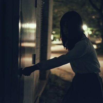 「意を決して扉に手をかける女性」の写真素材