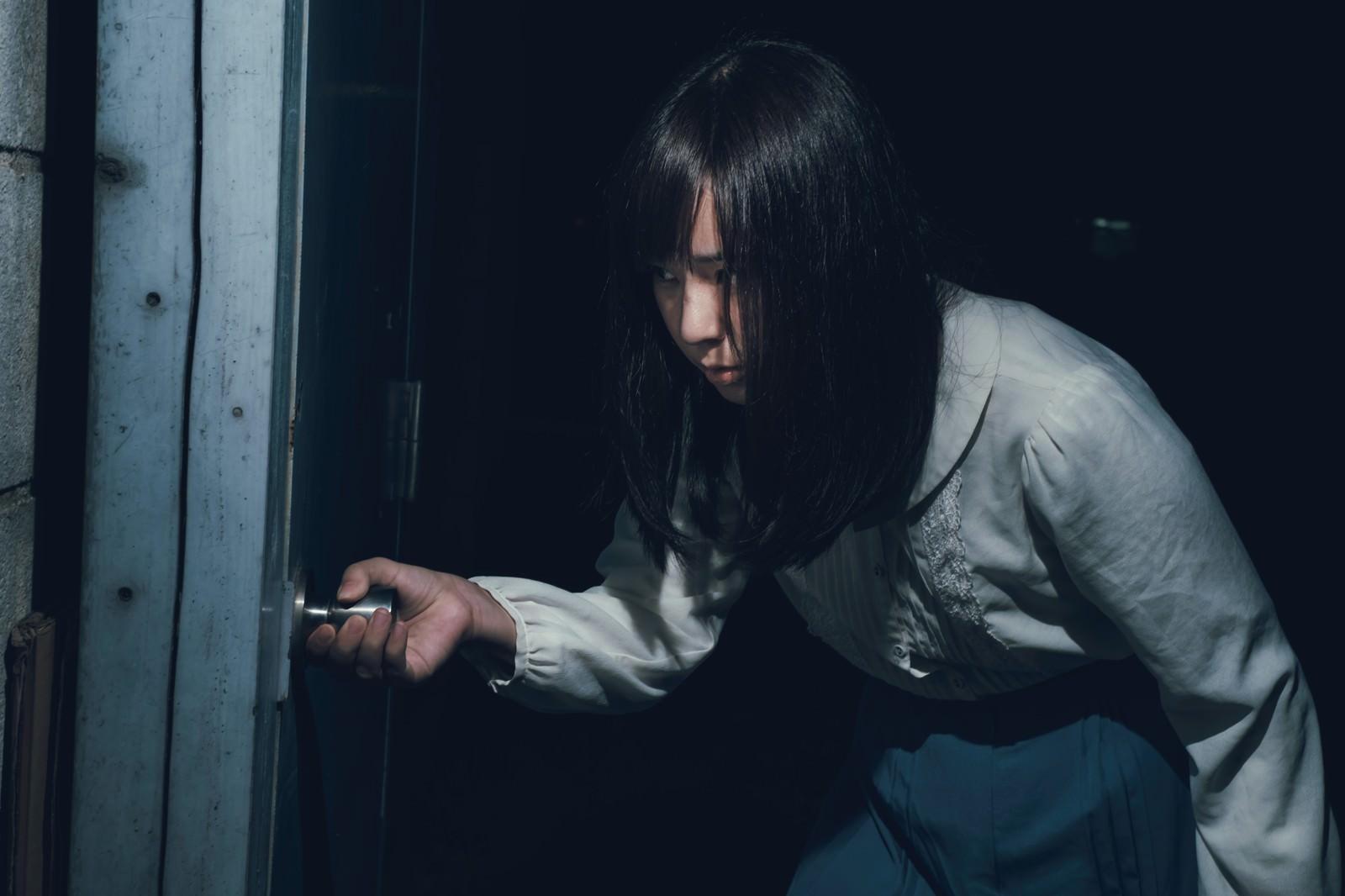 「恐る恐る扉を開ける女性」の写真[モデル:さとうゆい]
